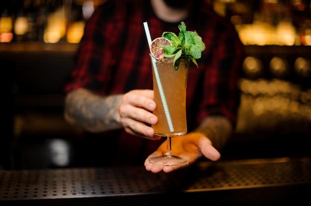Бармен держит бокал вкусного напитка sherry cobbler, украшенного листьями мяты и ломтиком апельсина