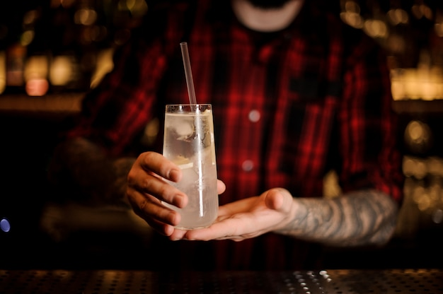 Barman holding elegant long drink glass filled with tom collins cocktail