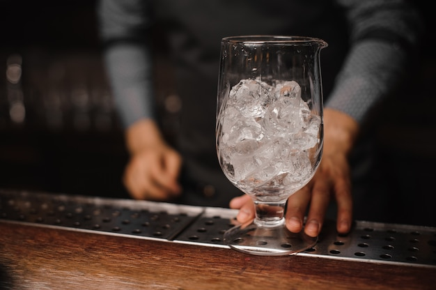 Barman holding a glass filled with ice cubes