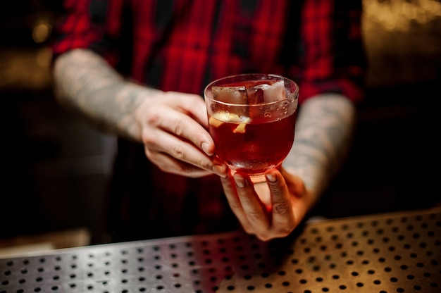 Barman holding a strong alcoholic drink with whiskey and orange peel on the bar counter