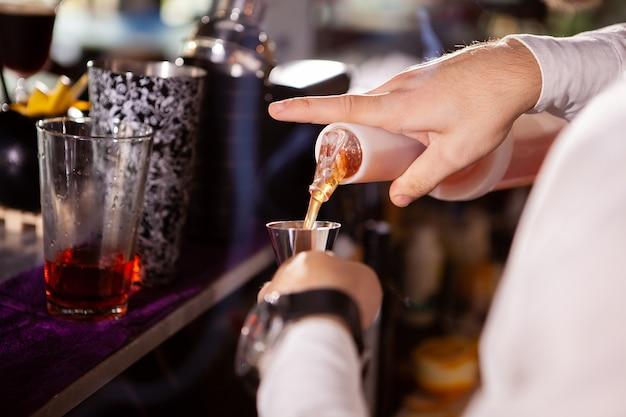 カクテルのために信じられないほどの飲み物を注ぐ白いシャツのバーテンダー