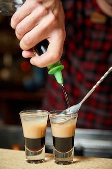 Бармен делает алкогольные шоты с ромом и ликером
