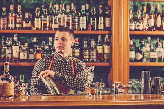The barman making an alcoholic cocktail at the bar counter on the bar space