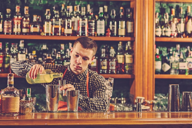 Barman making an alcoholic cocktail at the bar counter on the bar