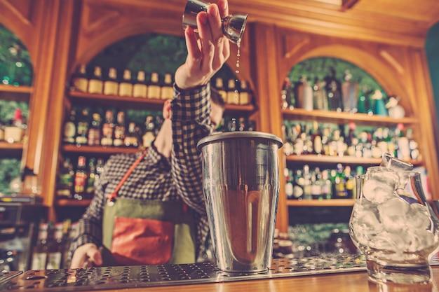 Barman che prepara un cocktail alcolico al bancone del bar