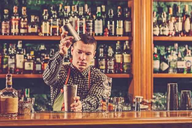 Бармен, делая алкогольный коктейль за барной стойкой в баре