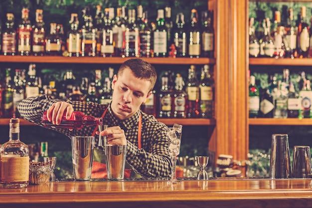バーカウンターでアルコールカクテルを作るバーテンダー