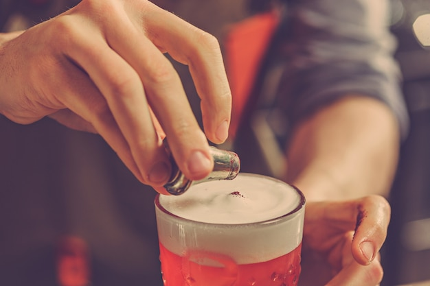 Бармен готовит алкогольный коктейль у стойки бара