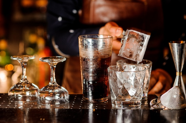 Barman making a cocktail and putting an ice cube into the glass