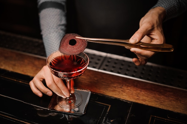 Barman making a red decorated alcoholic drink