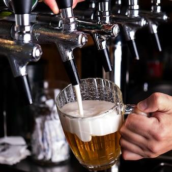 Бармен наливает пиво в стакан. крупный план