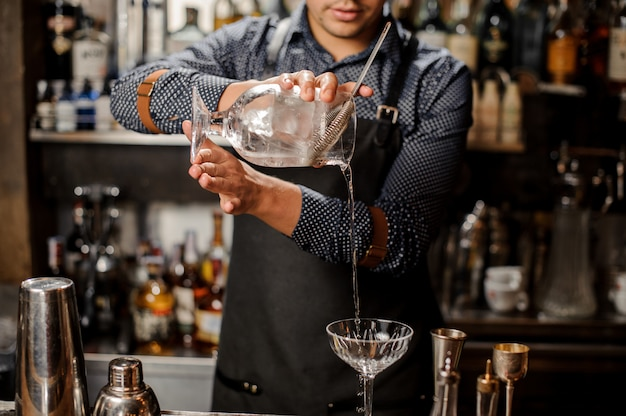 Barman pouring cold alcoholic drink into a cocktail glass