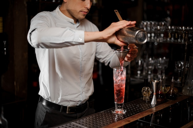 Barman pouring and cold strawberry mojito summer cocktail into the glass