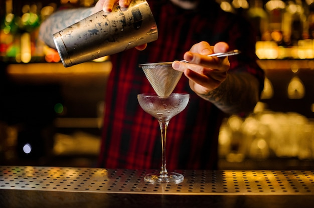 Barman pouring fresh alcoholic drink into an elegant glass using a strainer on the bar