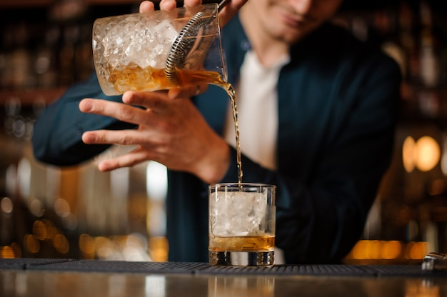 Barman pouring fresh and cold alcoholic drink into a glass