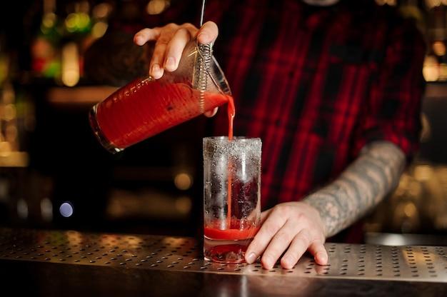 Бармен наливает свежий соленый красный томатный алкогольный напиток в стакан на барной стойке