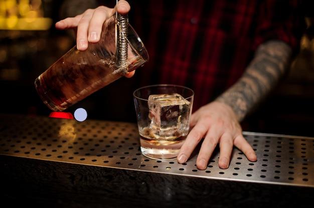 新鮮な強いウイスキーカクテルをグラスに注ぐバーテンダー