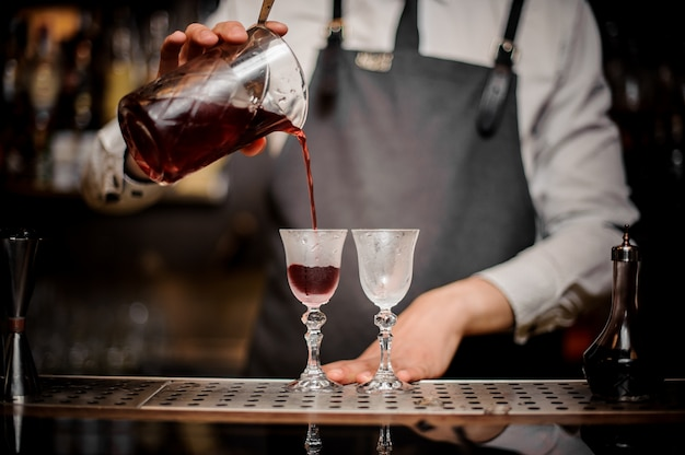 グラスに新鮮な夏のアルノーカクテルを注ぐバーマン