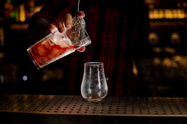 Barman pouring fresh and tasty bittersweet red cocktail into an empty cocktail glass on bar