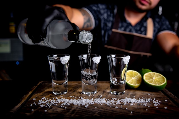 Barman pouring hard spirit into small glasses such as alcoholic shots of tequila or strong drink