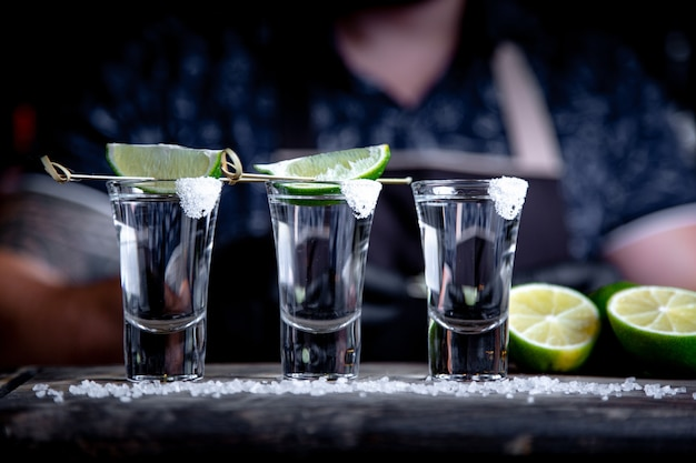 Barman pouring hard spirit into small glasses such as alcoholic shots of tequila or strong drink.