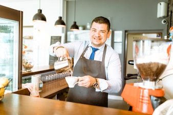 Barman pouring milk in coffee