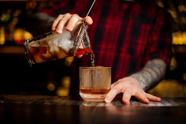 Barman pouring strong alcoholic cocktail of whiskey using strainer into the glass on the bar counter