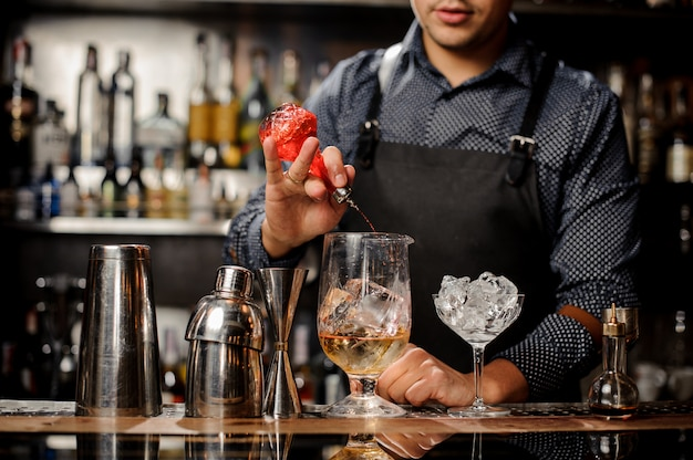 Barman pouring sweet fruit syrup into the large cocktail glass