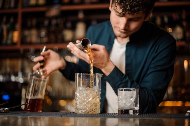 Barman pouring sweet syrup into a jar with ice making an alcoholic drink
