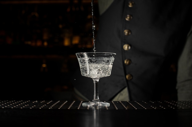 Barman pouring a transparent alcoholic cocktail into glass