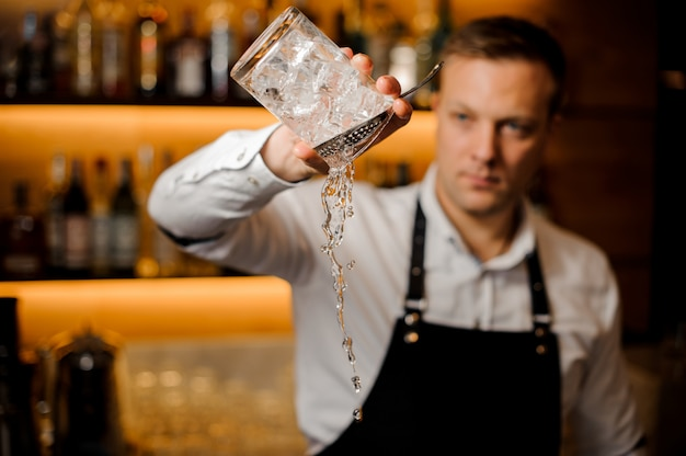 Barman pouring water from a glass with ice cubes