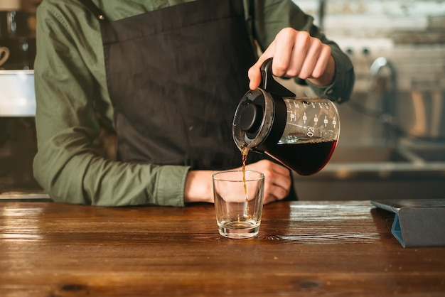 Barman pours coffee in a glass.