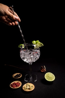 Barman preparing a gin and tonic cocktail on a black background