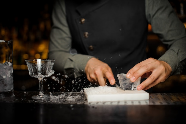 Barman preparing a large rectangular piece of ice n the plastic desk