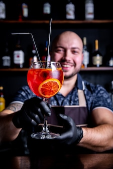 Barman puting to glass of fresh and tasty aperol syringe cocktail peace of ice