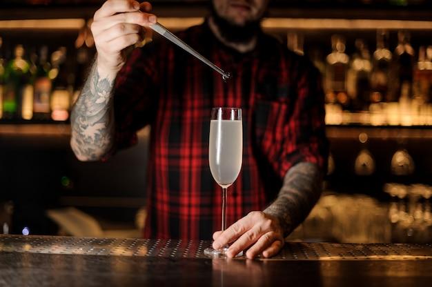 Бармен кладет вишню в французский коктейль 75