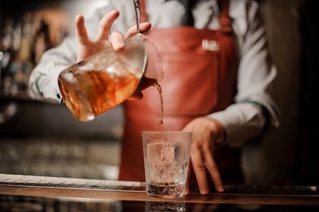 アルコールカクテルを作るバーのインテリアにバーマンの手。