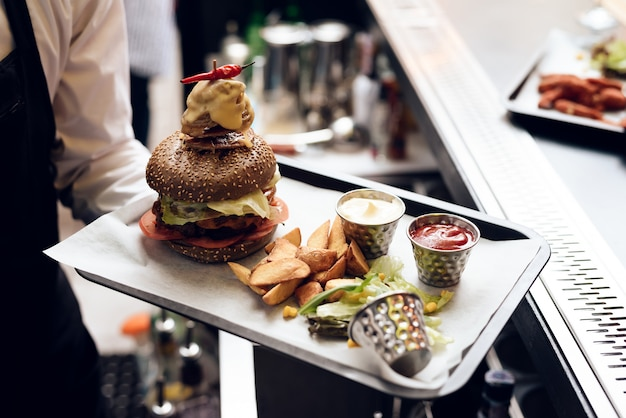 The barman serves a burger for people.