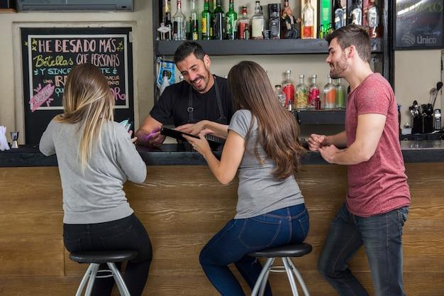 Barman showing menu to customers in the bar