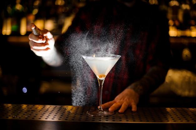 Barman spraying bitter on the elegant glass