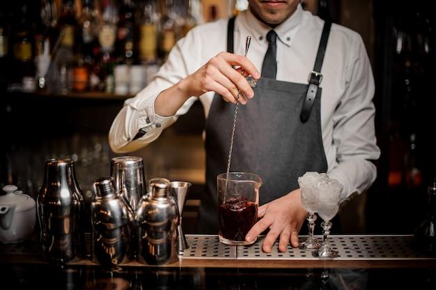 ガラスの新鮮な夏のアルコールカクテルを攪拌バーテンダー