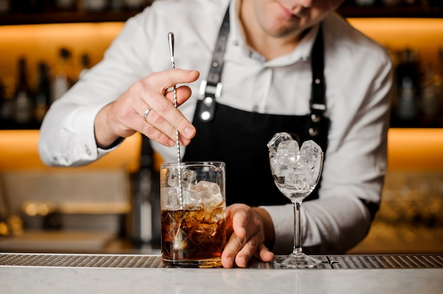 Barman stirring ice cubes with alcoholic drink