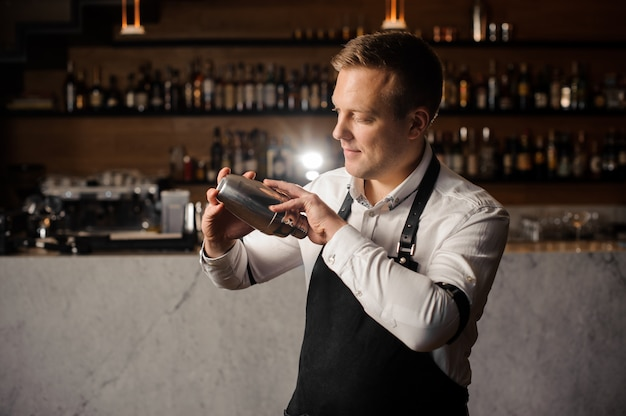 Barman in a white shirt and apron holding a shaker against the bar counter