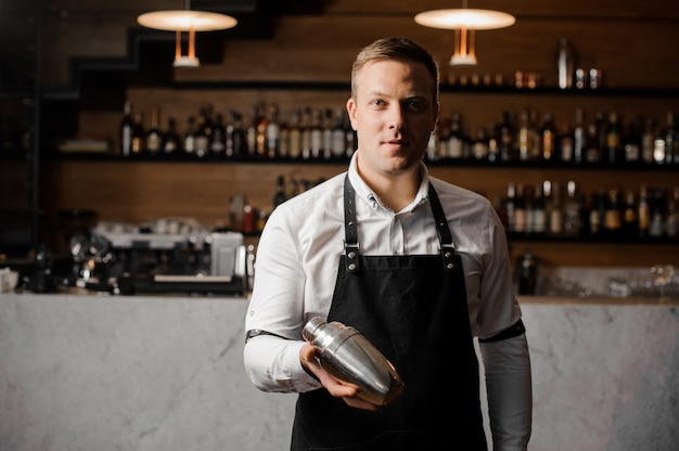Barman in white shirt and apron holding a shaker