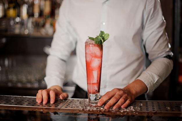 Бармен с бокалом вкусного свежего и сладкого клубничного мохито, летний коктейль