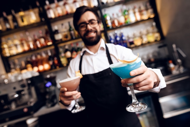 The barman with a beard prepared a cocktail at the bar.