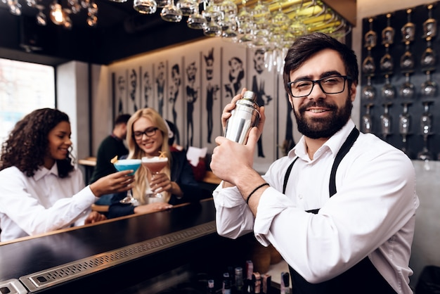 A barman with a beard prepares a cocktail at the bar.