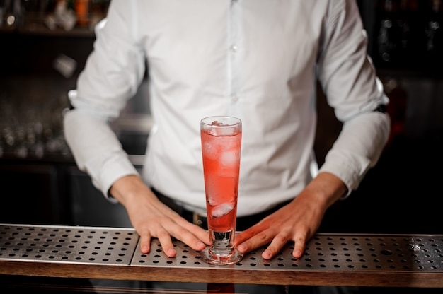 Barman with a glass of tasty fresh and sweet red summer cocktail
