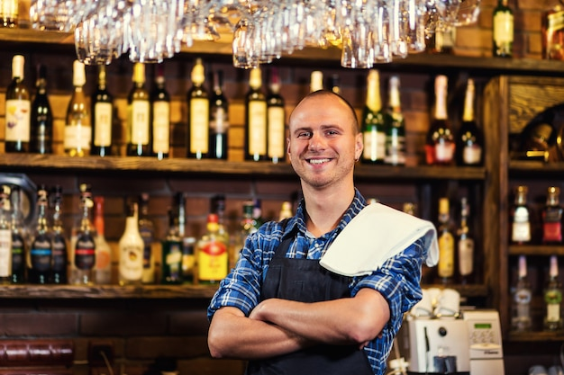 Barman at work in pub,portrait of cheerful barman worker standing,waiter giving menus,a pub.bar.restaurant.classic.evening.european restaurant.european bar.american restaurant.american bar.