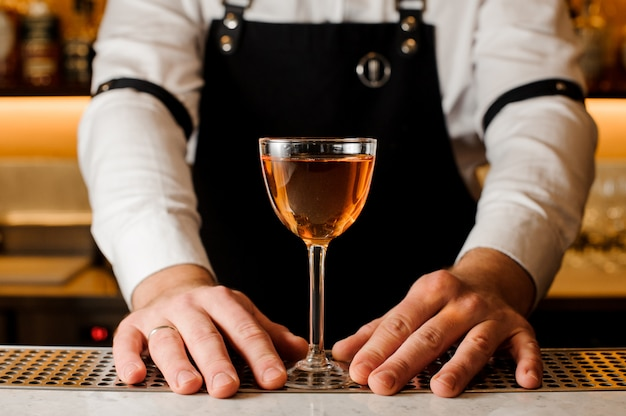 Barmans hands holding a glass with alcoholic drink